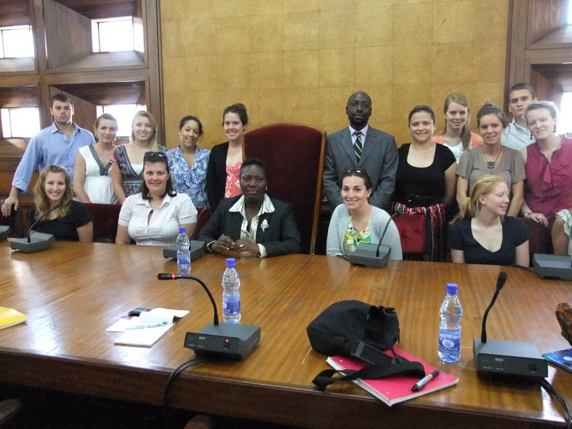 A group of students and Dr. Rubongoya in a government building