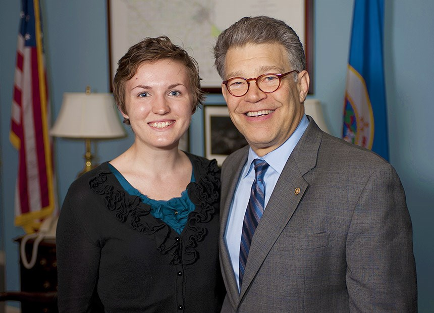 Student posing with a senator for a photo