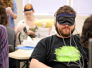 Student wearing an eyemask that records data