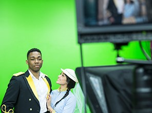 Two students acting in front of a green screen