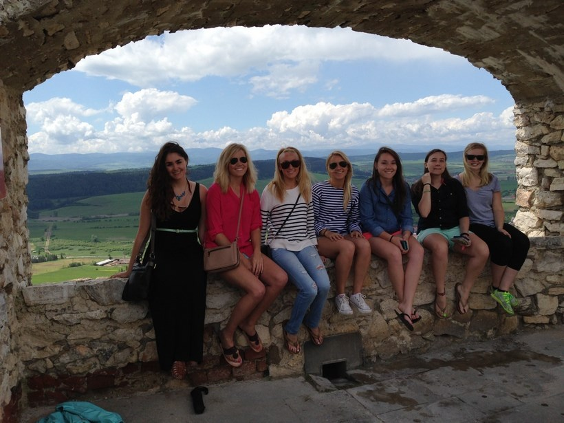 Students sitting on a rock ledge in Slovakia