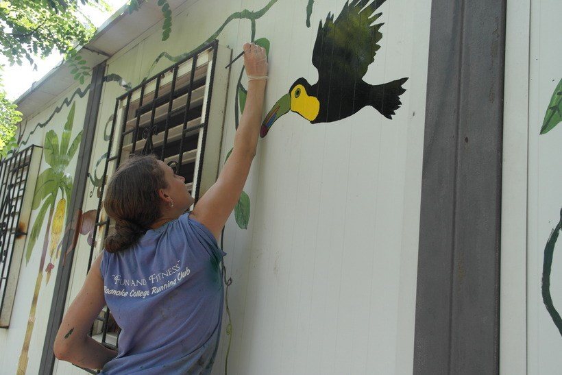 Student painting a mural on the side of a building