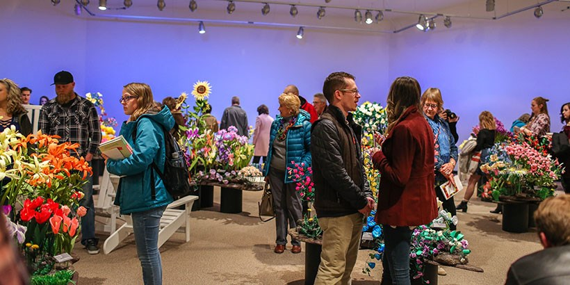 View of the gallery reception, flowers and people