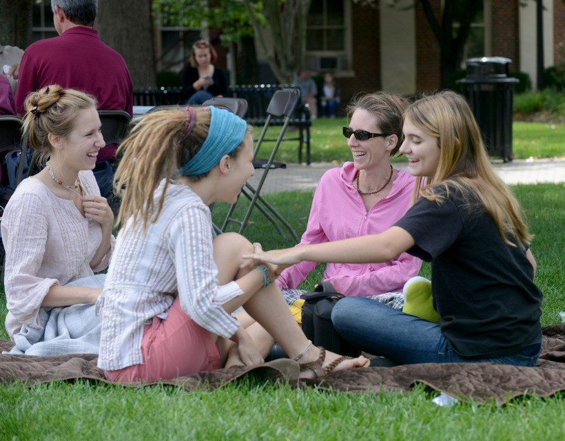 Families sitting on the lawn in the quad
