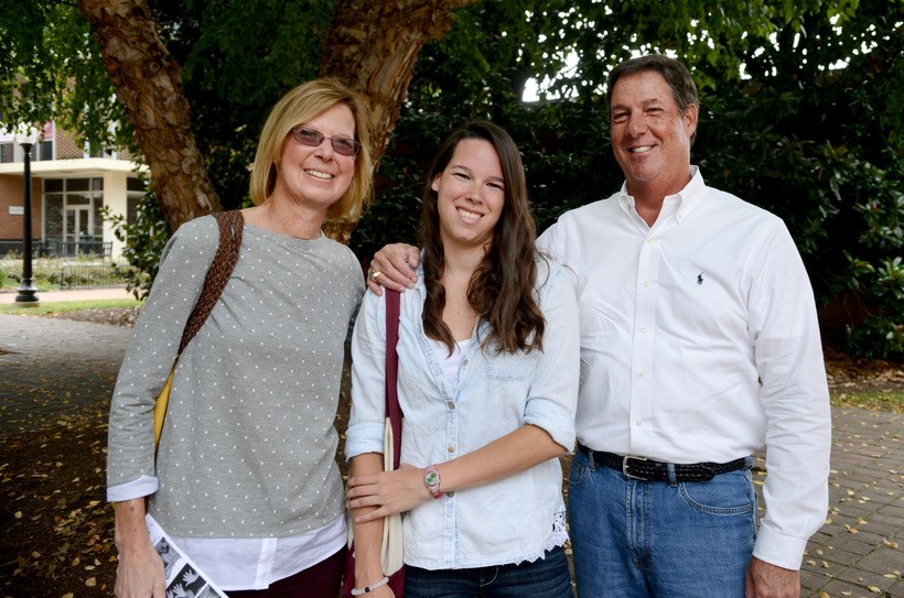 Student posing for a photo with her parents