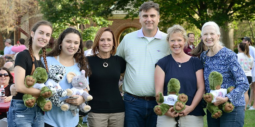 A family posing with their stuffed animals they made