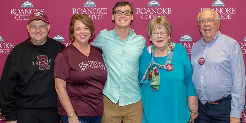 A family posing for a photo in front of the Roanoke College backdrop