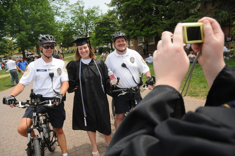 Campus safety posing with a senior in her graduation cap and gown