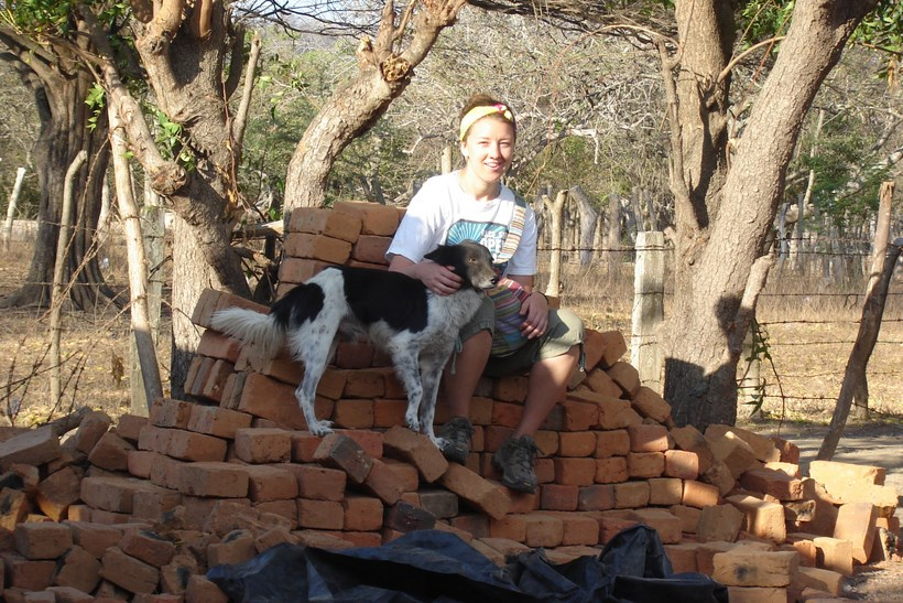 Student with a dog sitting on top of a pile of bricks