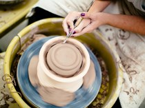 student working on pottery wheel