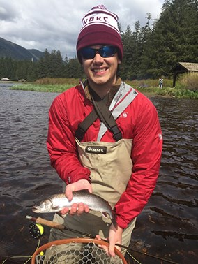Student with a fish he caught while fly fishing