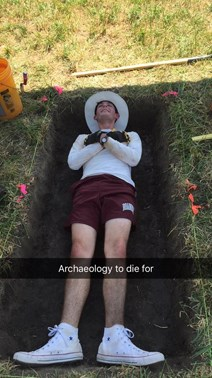 Jacob Friedrich laying in a fake grave. Caption: Archaeology to die for