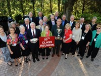50th Class Reunion Alumni pose with two trophies