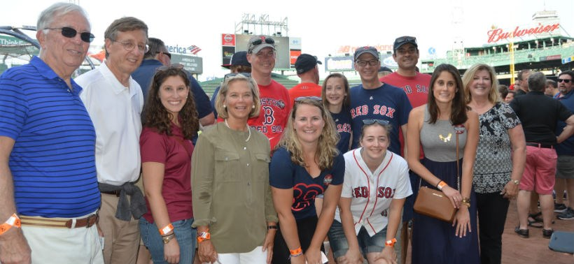 Alumni pose for a photo at the Red Sox game with Mrs. Maxey