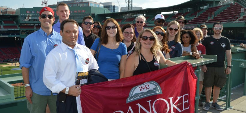 Roanoke College Alumni take picture with the College's flag at a Red Sox game