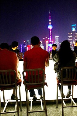Students sitting at a rooftop bar with the city skyline behind them at night