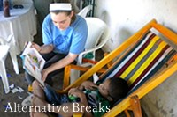 A RC student reading to a young child on a alternative break trip