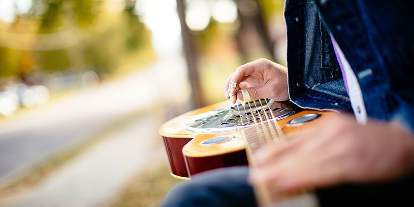 Closeup of student holding a guitar