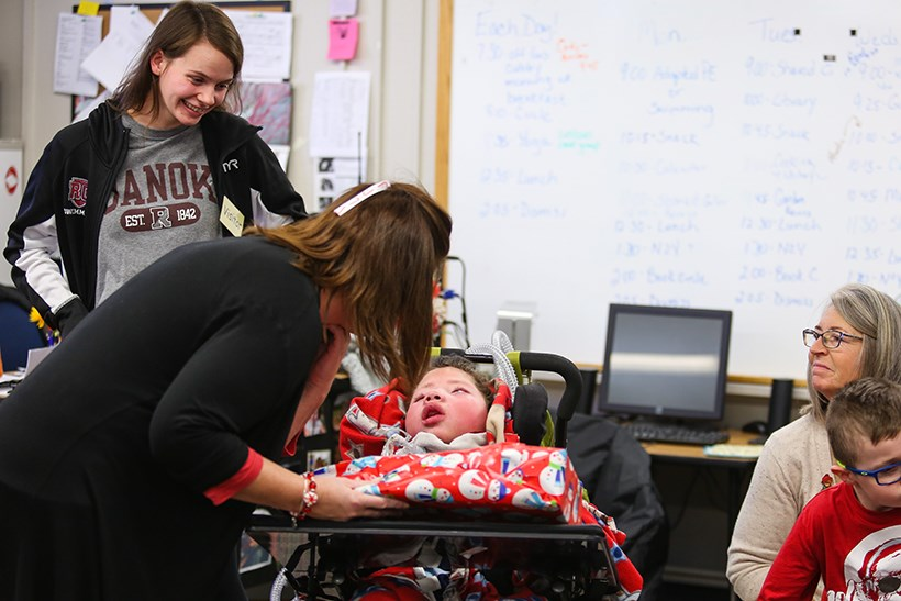 Student in wheelchair receiving toy.